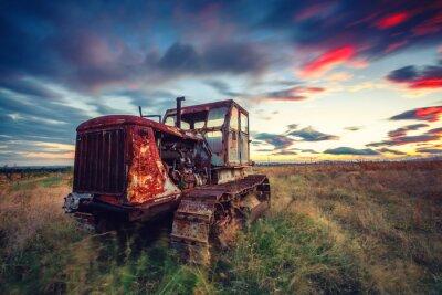 Plakat Piękny zachód słońca nad pole i stary zardzewiały ciągnika