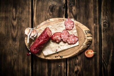 Plakat Plastry salami z czosnku na drewnianym pniu.