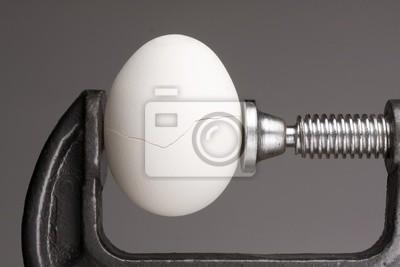 Plakat Pod ciśnieniem. Pękanie jajek pod naciskiem przez ściskanie zacisków z boków.