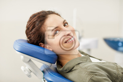 Plakat Portrait of smiling young woman lying in dental chair and looking at camera, copy space