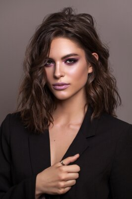 Plakat Portrait of young beautiful brunette model with violet professional make up, trendy wavy hairdo and perfect skin.