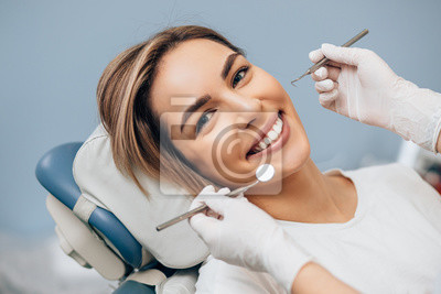Plakat portrait of young caucasian woman with perfect smile in dental office, come to treat spoiled teeth, look at camera