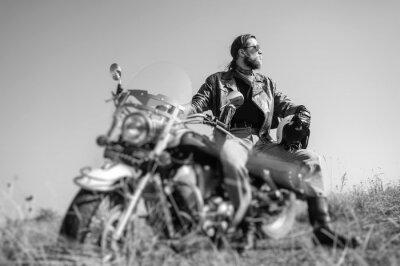 Plakat Portret młodego mężczyzny z brodą siedzący na jego krążownika motocyklu i patrząc na słońce. Mężczyzna ma na sobie skórzaną kurtkę i niebieskie dżinsy. Niski punkt widzenia. Plandeka obiektyw efekt ro