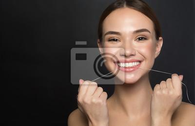 Plakat Portret pozytywna młoda kobieta która dba o jej zęby. Trzyma nić dentystyczną i śmieje się, patrząc z radością na aparat. Odizolowane i skopiuj miejsce po lewej stronie. Pojęcie zdrowia stomatologiczn