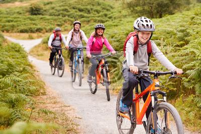 Plakat Pre-teen chłopiec jedzie na rowerze górskim z siostrą i rodzicami podczas rodzinnej wycieczki na kemping, z bliska