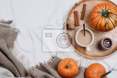 Plakat Przytulny flatlay z drewnianą tacą, filiżanką kawy lub kakao, świecą, dyniami na białych prześcieradłach i kocach