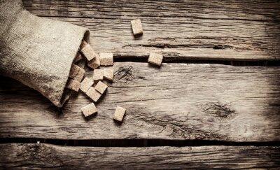 Plakat rafinowany cukier trzcinowy w worku. Na drewnianym tle.