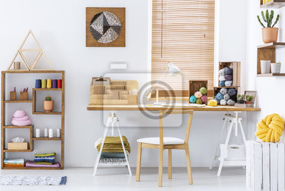 Plakat Real photo of a creative room interior with a desk, threads, knitting wool and graphic on a wall