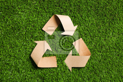 Plakat Recycling symbol cut out of kraft paper on green grass, top view