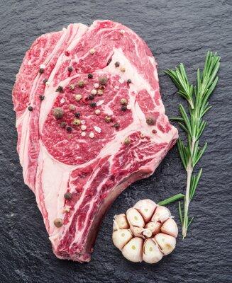 Plakat Rib eye steak z przyprawami na czarnym tle.