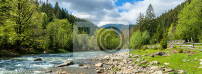 Plakat river in mountains. wonderful springtime scenery of carpathian countryside. blue green water among forest and rocky shore. wooden fence on the river bank. sunny day with clouds on the sky
