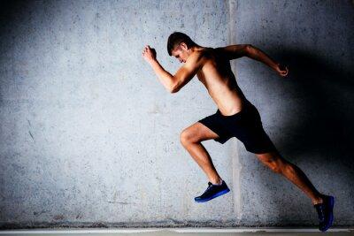 Plakat Runner sprint przed betonową ścianą w garażu