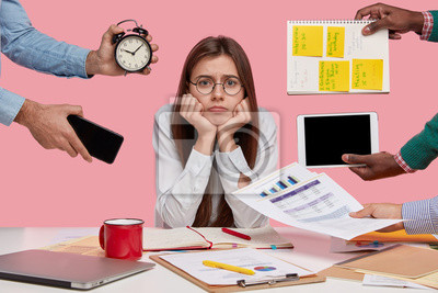 Plakat Sad female workaholic keeps hands under chin, busy making project work, studies papers, wears elegant white shirt, sits at desktop, unknown people stretch hands with notes, alarm clock, smartphone