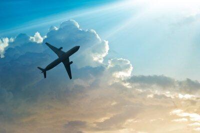 Plakat Samolot na niebie i chmury o wschodzie słońca