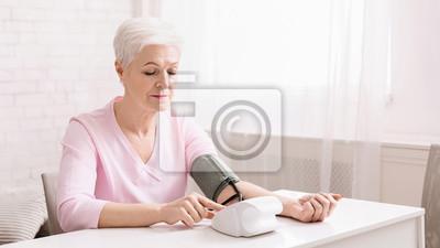 Plakat Senior woman measuring her blood pressure at home.