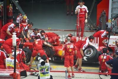 Plakat Sepang F1 Circuit, Malezja - 02 kwietnia 2010 - załoga Scuderia Ferrari Marlboro zespołu wyścigowego F1 opony zmieniają się podczas uprawiania Grand Prix Malezji Petronas 2010 2-4 kwietnia Sepang.