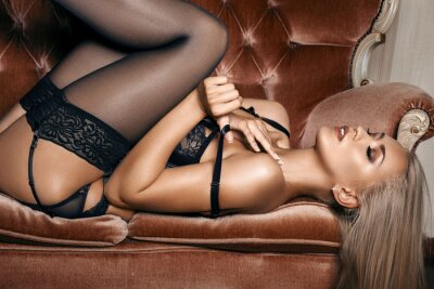 Plakat sexy woman in seductive black lingerie lying on a couch in stockings