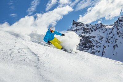 Plakat Skier skiing downhill in high mountains