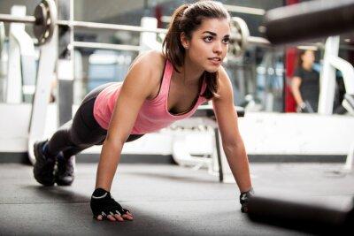 Plakat Śliczna brunetka pracuje w siłowni