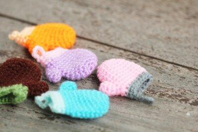 Śliczne małe szydełkowe skarpety i rękawiczki dziania działa na tle podłogi z drewna. Koncepcja na wakacje