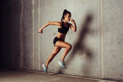 Plakat Slim atrakcyjna sportsmenka uruchomiony przed betonowym tle