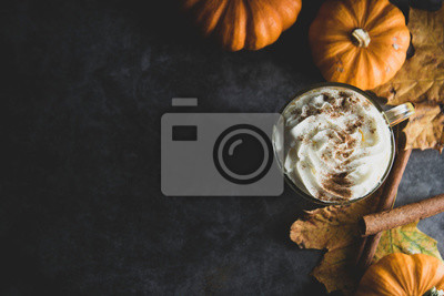 Plakat Spiced autumn pumpkin latte drink with cinnamon and cream foam top view with copy space fall drink