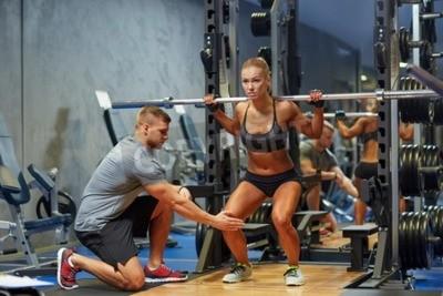 Plakat sport, fitness, pracy zespołowej, kulturystyka i ludzie Koncepcja - młoda kobieta i trener osobisty z sztangą wyginanie mięśni w siłowni
