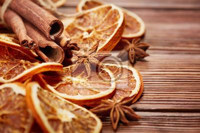 Plakat suche plasterki pomarańczy, laski cynamonu i anyżu na drewniane tła