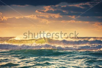 Plakat Sunrise and shining waves in ocean