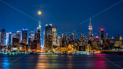 Plakat Super Moon above New York skyline. The top of the Empire State Building is illuminated with the colors of the German and Argentinian flags in honor of the Soccer World Cup final.