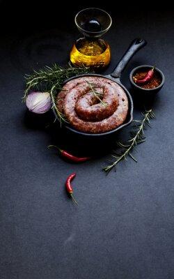 Plakat Surowe kiełbasy wołowiny na patelni żeliwnej, selektywnym focus