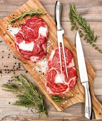 Plakat Surowe mięso świeże Ribeye Steak z ziół i przypraw na drewnianym biurku