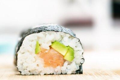 Plakat Sushi z łososia, awokado, ryż w wodorostów i pałeczki na drewnianym stole