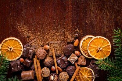 Plakat Świąteczne słodycze, czekoladki, przyprawy, trufle czekoladowe i suszonych pomarańczy na drewnianych backgroun z miejsca kopiowania tekstu. Poziomy