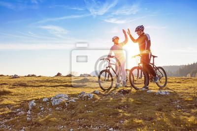 Plakat szczęśliwa para idzie na górskiej asfaltu drogowego w lesie na rowery z hełmami dając sobie wzajemnie wysoki piąty