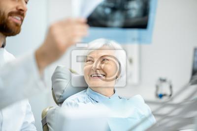 Plakat Szczęśliwa starszej kobiety kobieta podczas konsultacji z przystojnym dentystą pokazuje panoramicznego promieniowanie rentgenowskie w stomatologicznym biurze