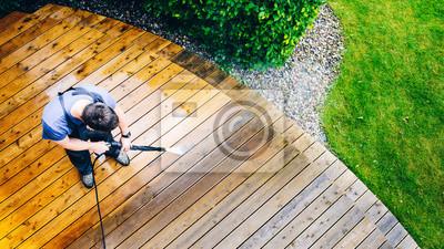 Plakat taras do sprzątania z myjką mechaniczną - myjka wysokociśnieniowa na drewnianej powierzchni tarasu