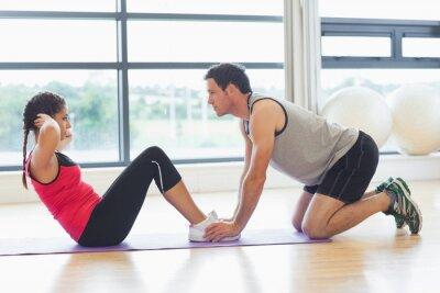 Plakat Trener pomaga kobieta robić brzuszków brzucha w siłowni