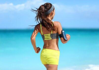Plakat Uruchamianie motywację - szkolenia biegacz z muzyką widziany zza jogging w modzie żółtym biustonosz sportowy rzemienie i neonowe spodenki strój na sobie bezprzewodowych słuchawek na plaży latem tle.