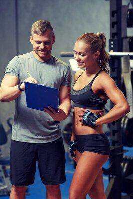 Plakat Uśmiechnięta młoda kobieta z osobistym trenerem w siłowni