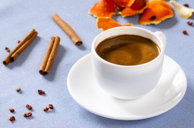 Plakat white cup with coffee and cinnamon sticks and orange skin, old wooden surface with place for your text