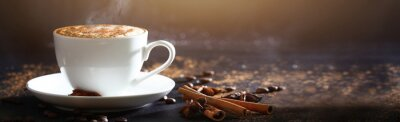 Plakat White cup with coffee with cinnamon on a gray background. Side view. Long banner. Solar flare from above.
