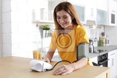 Plakat Woman checking blood pressure with sphygmomanometer at table indoors. Cardiology concept
