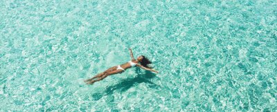 Plakat Woman in white bikini lying on transparent turquoise water surface on beach. Travel and vacations concept. Tropical background with empty space