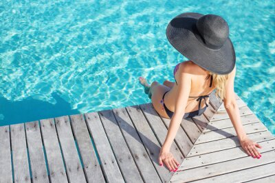 Plakat Woman sitting on the deck by the pool