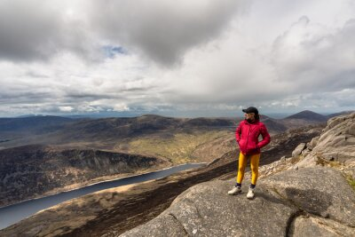 Plakat woman wearing cap, pink jacket, yellow leggings standing on top of mountain, with lake in background at Slieve Binnian Mountain North Ireland