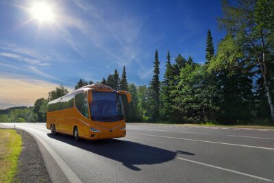 Yellow bus on the road at sunset carrying tourists on vacation
