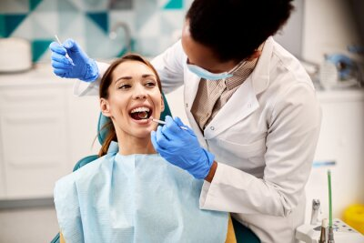 Plakat Young beautiful woman having her teeth examined during dental appointment at dentist's office.