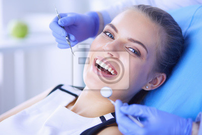 Plakat Young Female patient with open mouth examining dental inspection at dentist office.