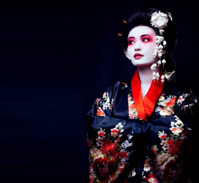 Plakat young pretty real geisha in kimono with sakura and decoration